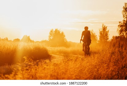 Cyclist on a gravel bike riding on a dusty trail in a field at sunset. Selective focus.
