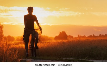 Cyclist on a gravel bike stands in a field on a dramatic sunset background. Beautiful landscape of young sports guy silhouette with bicycle in the field in the evening.