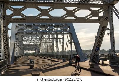 Cyclist on the John Seigenthaler pedestrian bridge or Shelby street crossing leaving downtown Nashville Tennessee