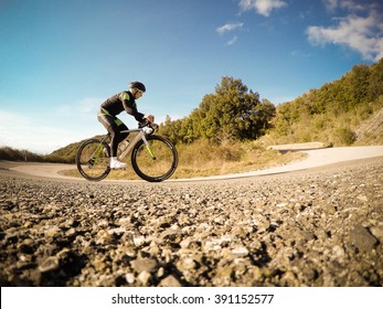 Cyclist on mountainous highway in a sunny day