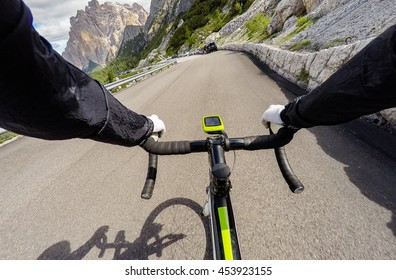 Cyclist on mountainous road in a sunny day. Cycling in Dolomites, Passo Valparola. POV Original point of view