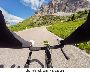 Cyclist on mountainous road in a sunny day. Cycling in Dolomites, Passo Falzarego. POV Original point of view.