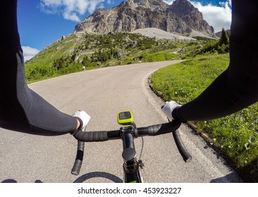 Cyclist on mountainous road in a sunny day. Cycling in Dolomites, Passo Falzarego. POV Original point of view. Fish eye effects