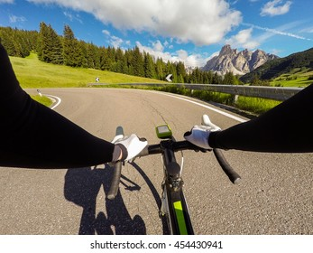 Cyclist on mountainous road in a sunny day. Cycling in Dolomites, Passo Campolongo. POV Original point of view
