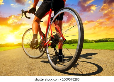 Cyclist on a road bike in the rural landscape at sunset.