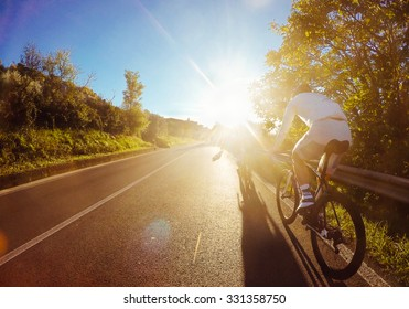 Cyclist on road bike in sunset. Cycling.