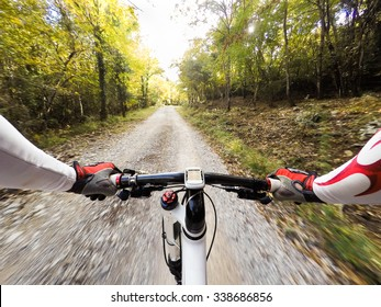 Cyclist on a road covered with leaves. Colors of autumn. POV Original Point of View