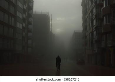 Radfahrer auf einer Straße in nebiger Stadt