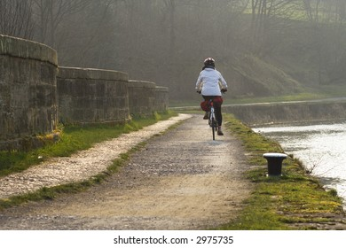 Cyclist on a towpath over an aqueduct by the Forth and Clyde Canal