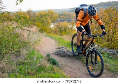 Cyclist in Orange Riding the Mountain Bike on the Autumn Rocky Enduro Trail. Extreme Sport and Enduro Biking Concept.
