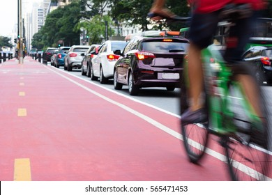 Cyclist passing bicycle lane while a row of cars are stuck in traffic. Motion blur