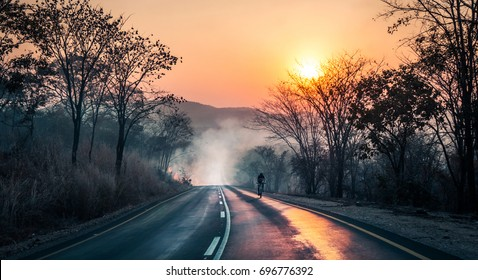 Cyclist passing fire and smoke with the sun reflecting on tarmac during sunset, on mountainbike riding in Zambian mountains,