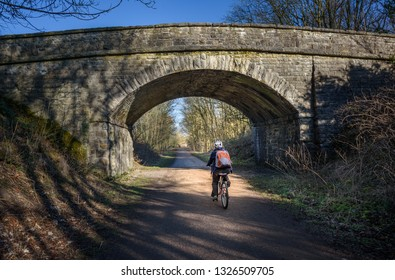 A cyclist passing under one of the railway viaducts on teh Monsal Trail, Derbyshire, Peak District, Uk.