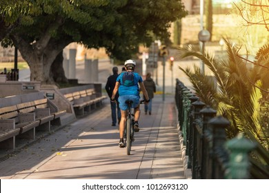 Cyclist pedaling his bike on a narrow street with stone wall and an old neighborhood