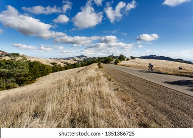 Cyclist powers up hill on bicycle in Mt Diablo Park on sunny day
