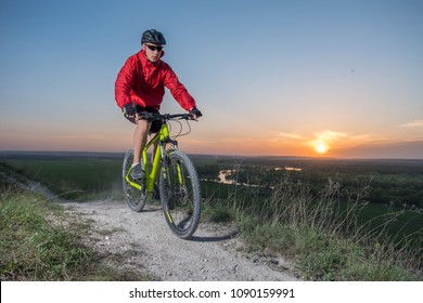 A cyclist in a red jacket rides a bike along the mountain path. The concept of extreme sports. Mountain bike.