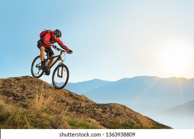 Cyclist in Red Jacket Riding the Bike in the Beautiful Mountains Down the Rock on the Sunrise Sky Background. Extreme Sport and Enduro Biking Concept.