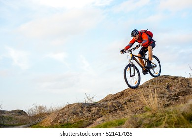 Cyclist in Red Jacket Riding the Bike Down Rocky Hill. Extreme Sport Concept.