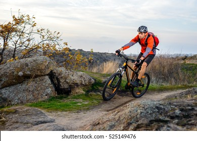 Cyclist in Red Jacket Riding the Bike on the Rocky Trail. Extreme Sport Concept. Space for Text.