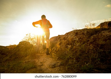 Cyclist in Red Picking his Mountain Bike up the Autumn Rocky Trail at Sunset. Extreme Sport and Enduro Biking Concept.