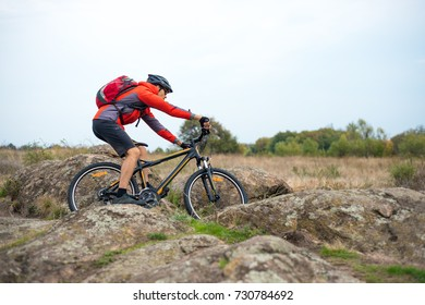 Cyclist in Red Riding the Bike on the Rocky Trail on the Sunset Sky Background. Extreme Sport and Enduro Biking Concept.
