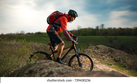 Cyclist in Red Riding the Bike on the Rocky Trail at Evening. Extreme Sport and Enduro Biking Concept.