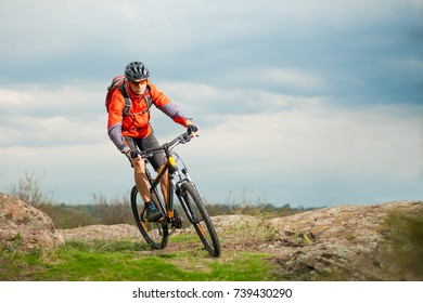 Cyclist in Red Riding the Bike on the Rocky Trail. Extreme Sport and Enduro Biking Concept.