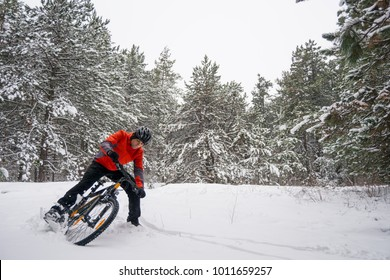 Cyclist in Red Riding the Mountain Bike in the Beautiful Winter Forest. Extreme Sport and Enduro Biking Concept.
