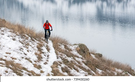 Cyclist in Red Riding the Mountain Bike on the Snowy Trail. Extreme Winter Sport and Enduro Biking Concept.