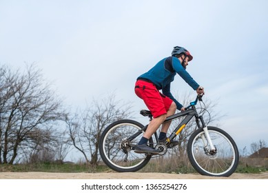 Cyclist in red shorts and blue sweater rides a bicycle, active lifestyle. Spring cycle.