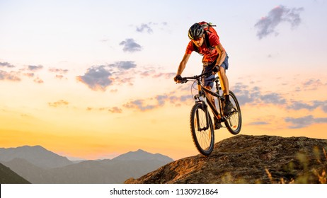 Cyclist in Red T-Shirt Riding the Bike in the Beautiful Mountains Down the Rock on the Sunset Sky Background. Extreme Sport and Enduro Biking Concept.