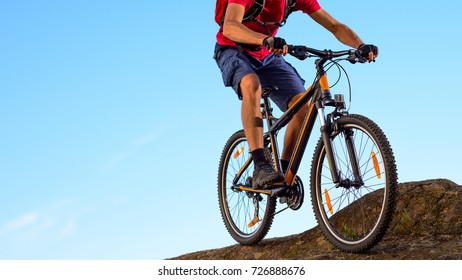 Cyclist in Red T-Shirt Riding the Bike Down the Rock on the Blue Sky Background. Extreme Sport and Enduro Biking Concept.