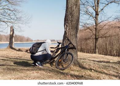 Cyclist repairing bike in the spring woods