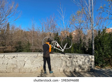 A cyclist repairs his bicycle at Madrid Rio Park in Madrid, Spain