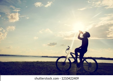 Cyclist resting and drinking water cycling silhouette at sunset. active outdoor lifestyle concept