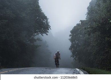 The cyclist ride his bicycle up high on hill, Cycling to destination no matter how bad weather is. Foggy, windy, raining and cold day. Foggy like blur background.