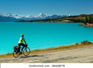 cyclist rides along the winding asphalt mountain road along Lake Pukaki view from Glentanner Park Centre near Mount Cook, on a background of blue sky with clouds, snowy Southern Alps.
