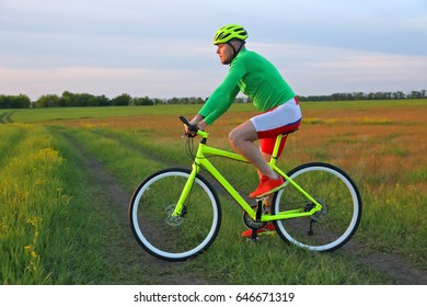 cyclist rides a bicycle in a field
