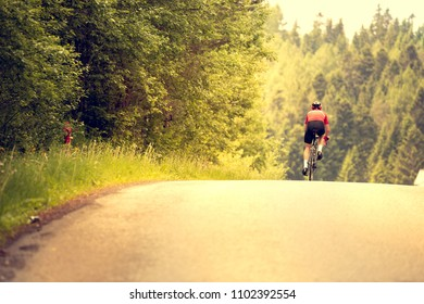 Cyclist rides a bicycle on an asphalt road. Sunset.