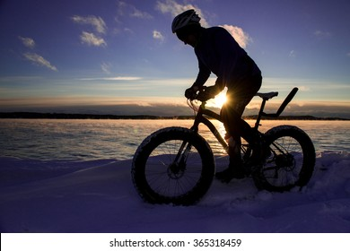 Cyclist rides fat tire bike in winter at sunset