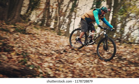 Cyclist rides his mountain bike trough the forest on man made track.