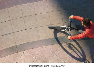 cyclist rides on the sidewalk path, top view.Spain, Jerez, January 2018