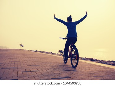 cyclist riding bike with arms outstretched in the coasts sunrise