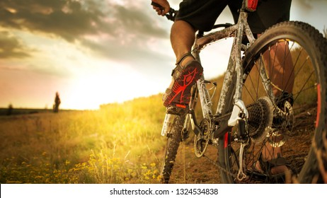 Cyclist riding the bike down rocky hill at sunset. Close up extreme sport concept