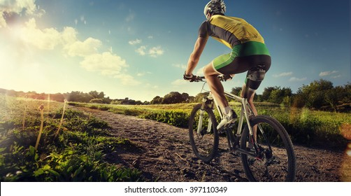 Cyclist riding a bike on an off road to the sunset