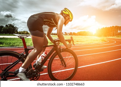 Cyclist riding a bike on an open Track to the sunset
