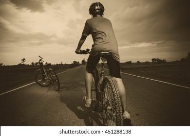 Cyclist riding a bike on an open road to the sunset