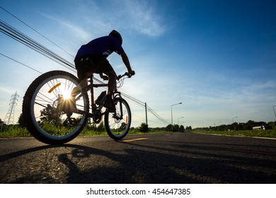 Cyclist riding a bike on an open road to the sunset, Thailand