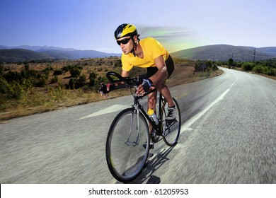 A cyclist riding a bike on an open road in Macedonia