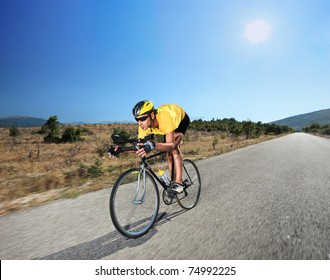 Cyclist riding a bike on an open road in Macedonia with a sun in the background